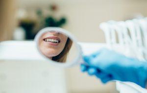 Tandarts toont spiegeltje aan patiënt