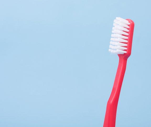 Rode tandenborstel tegen blauwe achtergrond