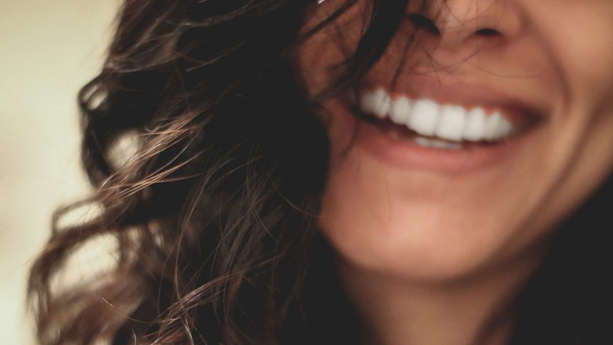 Close-upfoto van lachende jonge vrouw