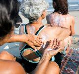 Drie vrouwen smeren elkaars rug in op het strand