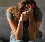 Vrouw met zwangerschapstest zit met handen in het haar.