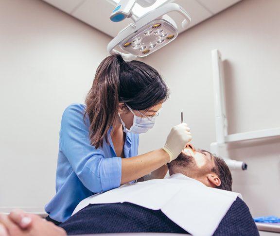 Vrouwelijke tandarts behandelt mannelijke patiënt