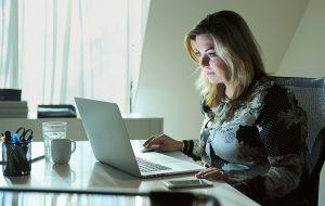 Vrouw kijkt op laptopscherm