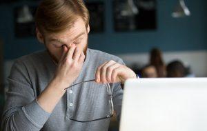 Persoon met droge ogen achter laptopscherm.