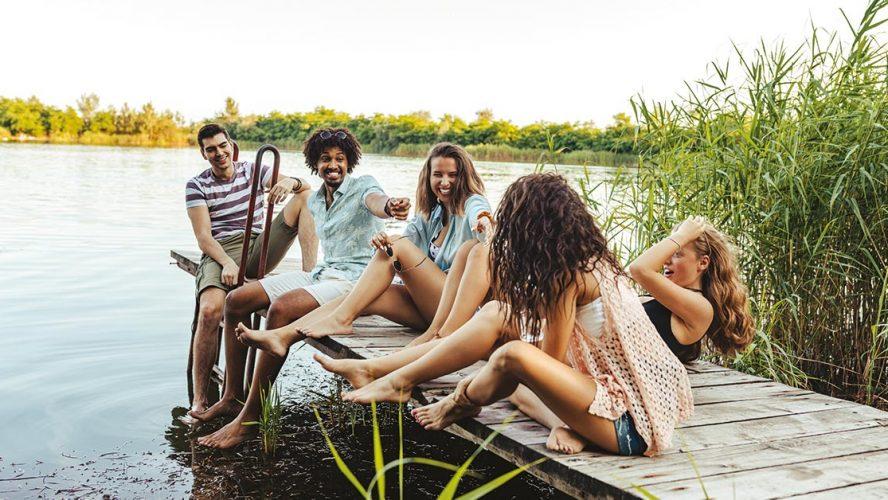 Lachende groep mensen bij het water