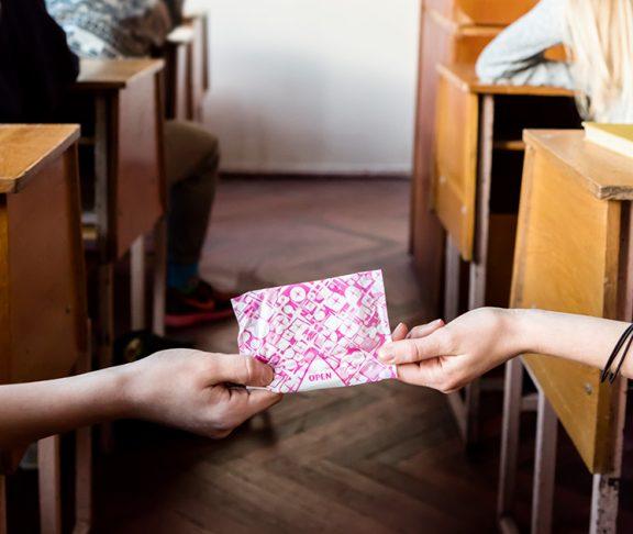Twee meisjes geven maandverband door in klaslokaal.