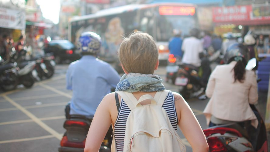Vrouw met rugzak in drukke straat.