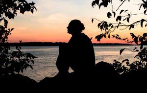 Silhoutte van vrouw aan het water.