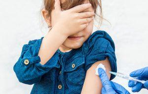 Jong meisje krijgt vaccin toegediend.