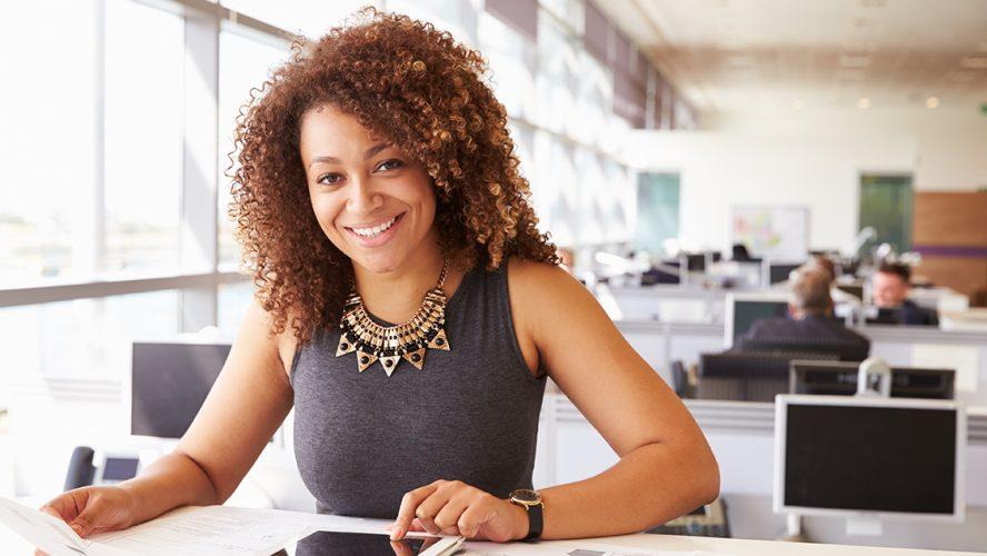 Jonge vrouw met blote armen in kantoor.
