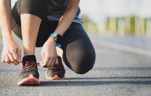 Sportief geklede vrouw vetert sportschoenen