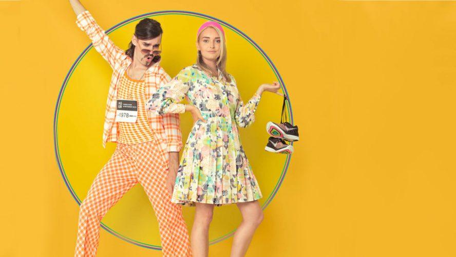 Jonge man en vrouw in kleurige kleding voor gele achtergrond.