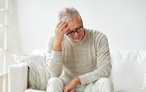 Oudere man zit op bank en kijkt met bezorgde blik.
