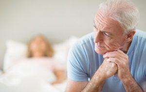 Oudere man zit aan de rand van het bed en kijkt met bedenkelijke blik uit het raam.