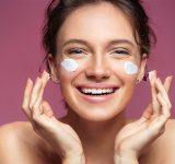 Vrouw smeert gezicht in met creme