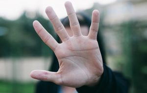 Man verbergt gezicht achter uitgstoken hand.