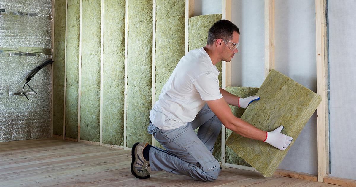 Werkman plaatst isolatiemateriaal in muur