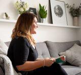 Vrouw met boek in haar woonkamer