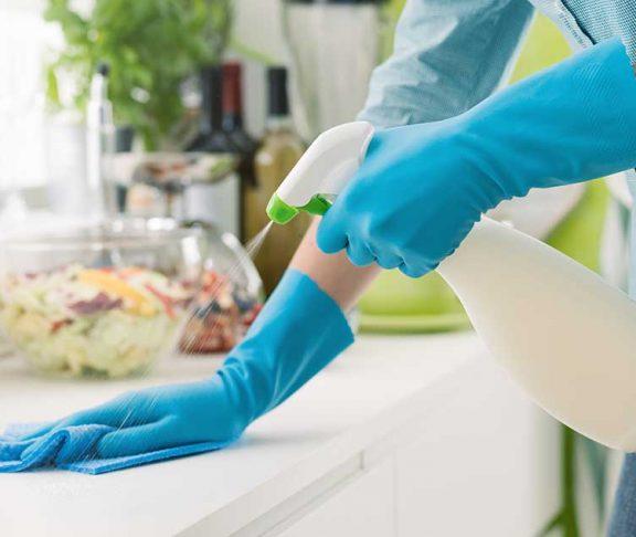 Vrouw met blauwe handschoenen maakt keukenaanrecht schoon met schoonmaakspray en doekje.
