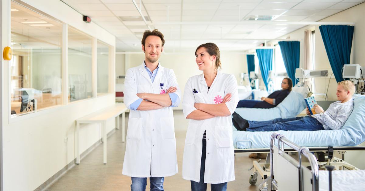 Onderzoekers staan in ruimte met ziekenhuisbedden