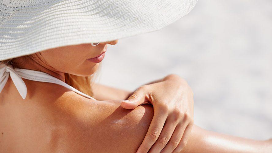 Vrouw met witte hoed smeert zonnebrand verstandig zonnen