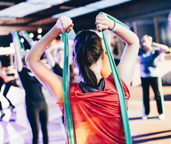 Vrouw tijdens sportles met weestandsbanden