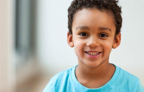 Jongen met kort bruin krulhaar, blauwe t-shirt
