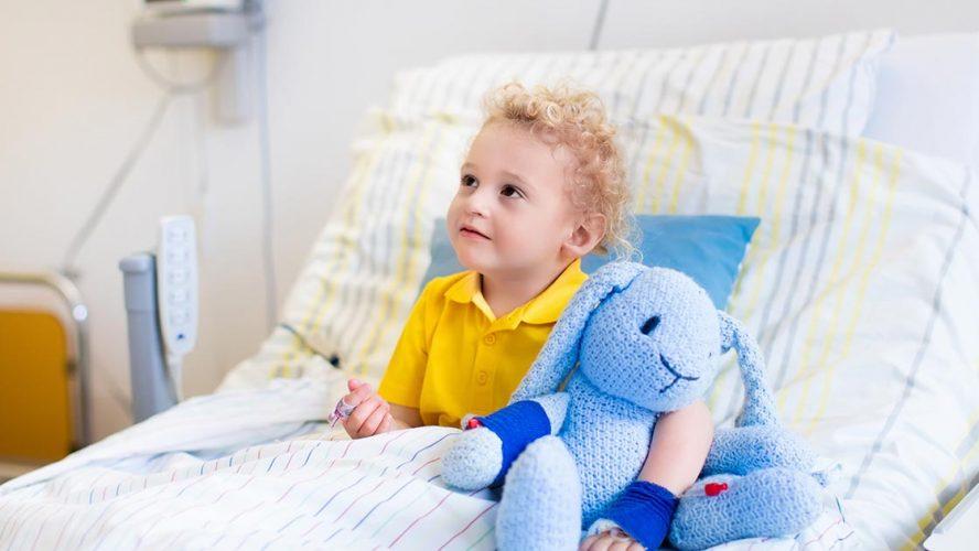 Jongen met blonde krullen op ziekenhuisbed met blauw knuffelkonijn.