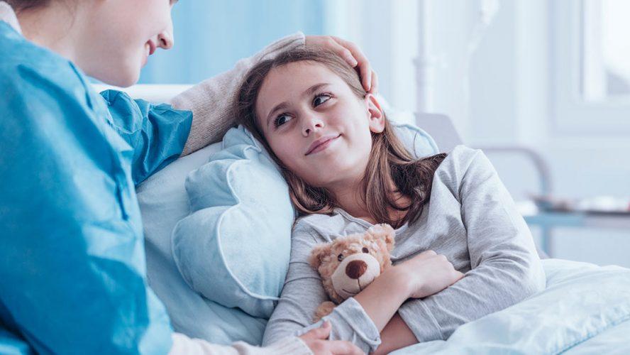 Meisje met knuffelbeer op ziekenhuisbed, glimlacht naar veprleegkundige.