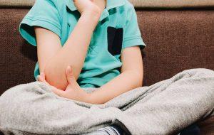 Concept kind met kinderreuma: kind grijpt naar pijnlijke elleboog
