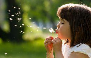 Kind blaast op paardenbloem
