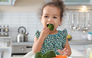 Schattige peuter eet broccoli