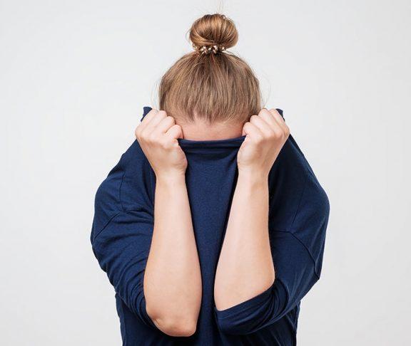 Onzekerheid over huidproblemen: jonge vrouw verbergt gezicht