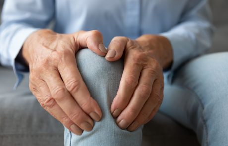 Old senior adult woman female hands touching knee sitting alone, retired elderly grandma feeling hurt joint pain in leg suffering from osteoarthritis bones disease or injury concept, close up view