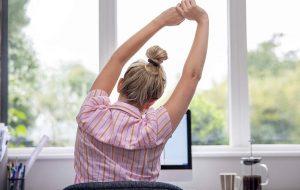 Vrouw strekt zich uit achter haar bureau