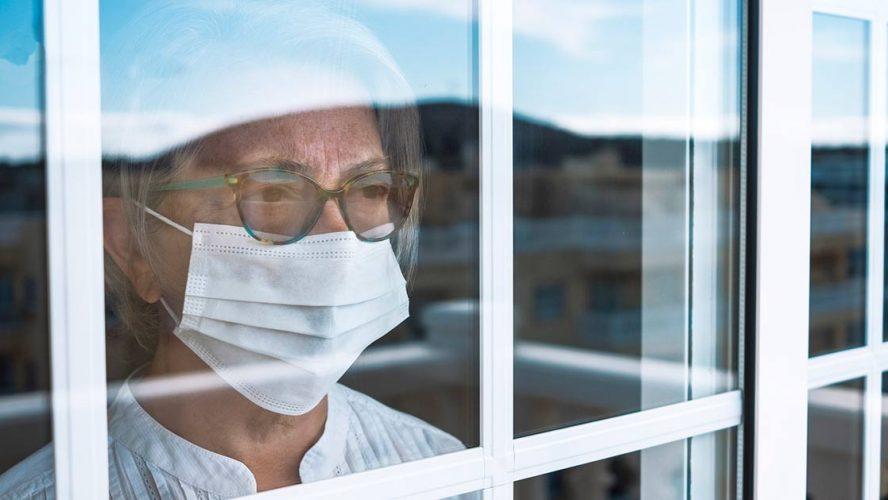 Oudere vrouw achter raam met mondkapje