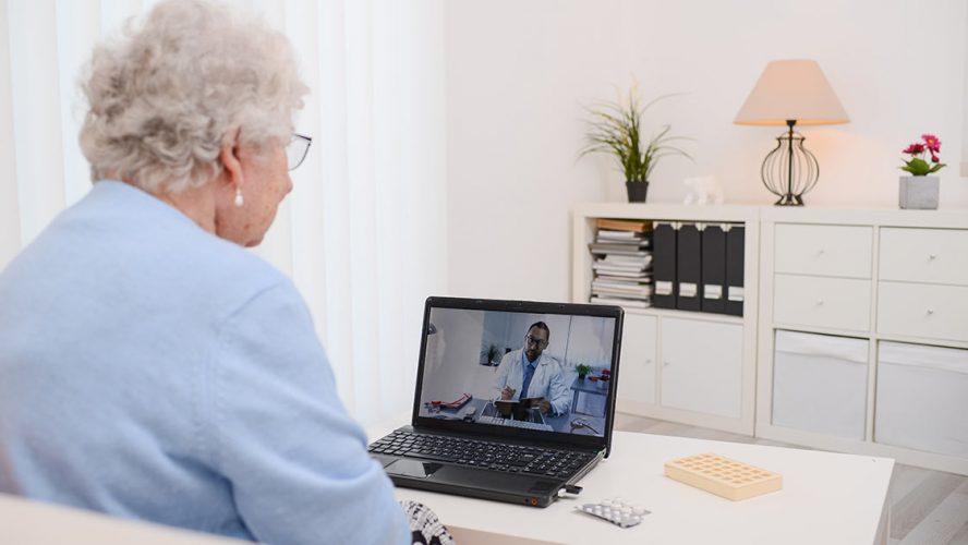 Oude vrouw zit op de bank met een digitaal consult met haar arts