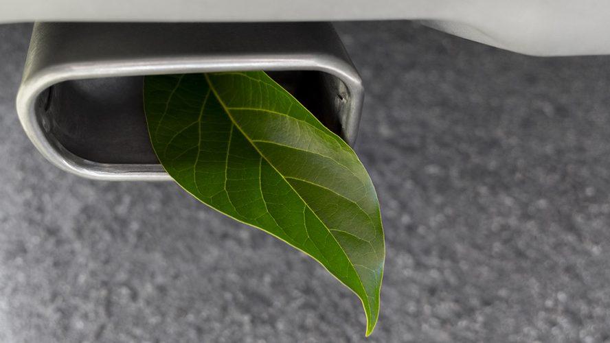 Auto-uitlaat met groen blaadje erin
