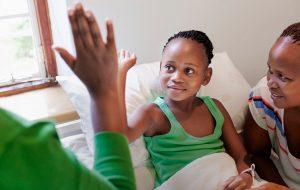 Kind in ziekenhuis geeft highfive aan dokter