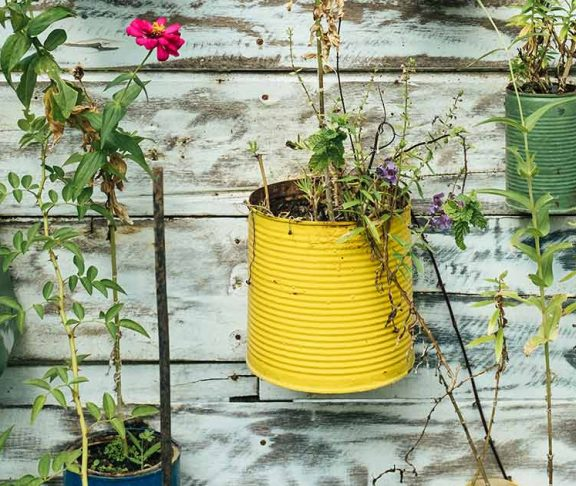 Blikken als bloempotten aan de muur