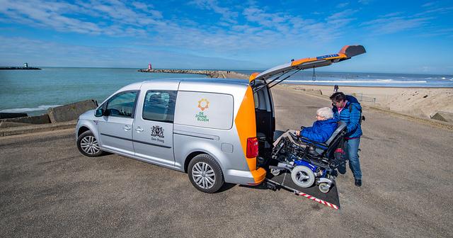 Een werknemer van de Zonnebloem helpt Magda uit de rolstoelwagen te stappen