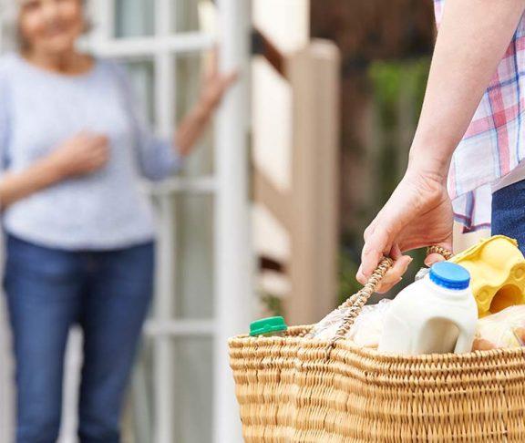 Vrouw brengt oude buurvrouw een tas met boodschappen