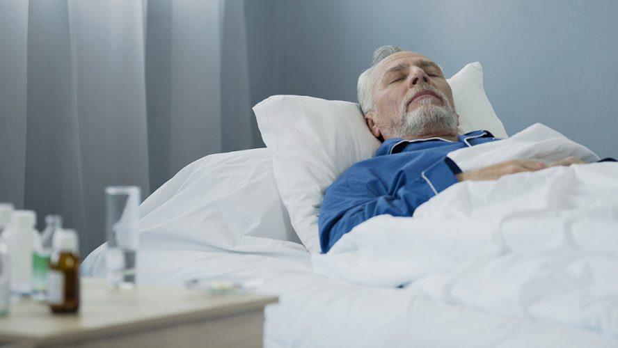 Oude man slaapt in ziekenhuisbed