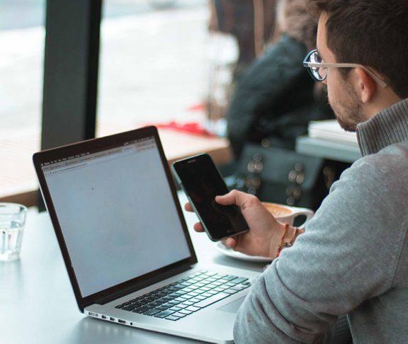 Jonge man met laptop maakt online betaling via smarthphone